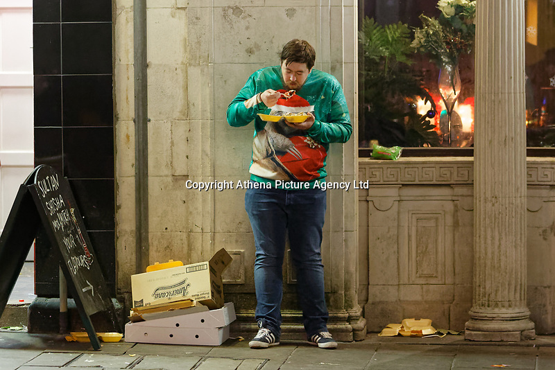 Pictured: A man in a Christmas jumper eats a take-away meal. Friday 14 December 2018<br /> Re: Revellers in Wind Street, Swansea, Wales, UK.