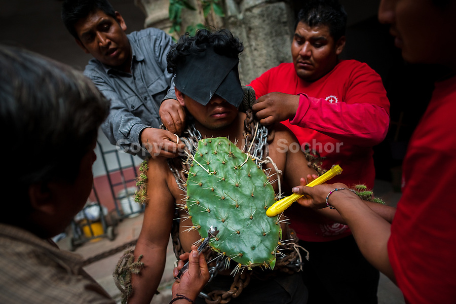 A hooded penitent is seen while a giant cactus is being attached to his body before the Holy week procession in Atlixco, Mexico, 30 March 2018. Every year on Good Friday, dozens of anonymous men of all ages voluntarily undergo pain and suffering during the religious procession of the 'Engrillados' (the Shackled ones) in Puebla state, central Mexico. Wearing heavy chains on their shoulders covered with prickling cacti while being burned by the hot midday sun, they recall Jesus Christ's death by crucifixion and demonstrate their religiosity and faith.