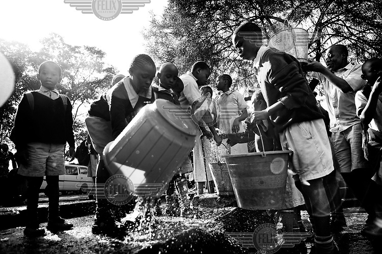Children collect drinking water in the schoolyard of the popular Olympic Primary School, one of the leading government schools in the country, in Kibera slum. Over 25 percent of Nairobi's population live in Kibera, an area that covers less than one percent of the city. Although the population of the slum is over one million, it is recognised officially as a 'squat', or illegally occupied land, which allows the government to ignore the basic needs of the inhabitants.