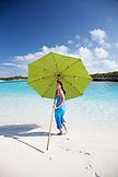 EXUMA, Bahamas. Nicole playing and carrying an umbrella on a sandbar.