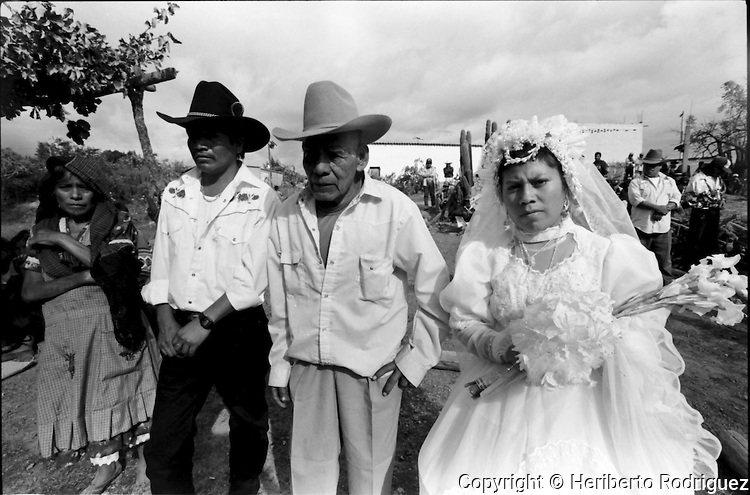 A Zapotec newly-married couple are welcomed by their relatives as they arrive at their house in Coatecas Altas village, Oaxaca, November 22, 1998. Most of the villagers of Coatecas leave their home to harvest in northern state of Sinaloa.  © Photo by Heriberto Rodriguez