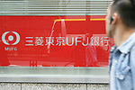 A man walks past a signboard of Bank of Tokyo-Mitsubishi UFJ on display outside its bank branch on May 17, 2017, Tokyo, Japan. Japan's biggest bank plans to shorten its name by dropping ''Tokyo'' to Bank of Mitsubishi UFJ. (Photo by Rodrigo Reyes Marin/AFLO)