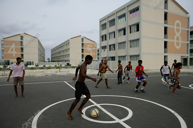 Young men play soccer against the backdrop of new numbered residential buildings on the island of Hulhumale, an artificial island standing 6 feet above sea level that is being built opposite Male, the capital of the Maldives. Since it is at a safer elevation that existing islands, the government is encouraging settlers from outlying islands to resettle there. The Maldives, April 2005.