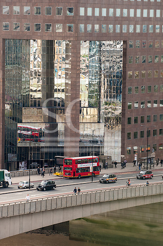 London, England. No 1 London Bridge with red bus and black cabs, reflection in modern mirrored building.