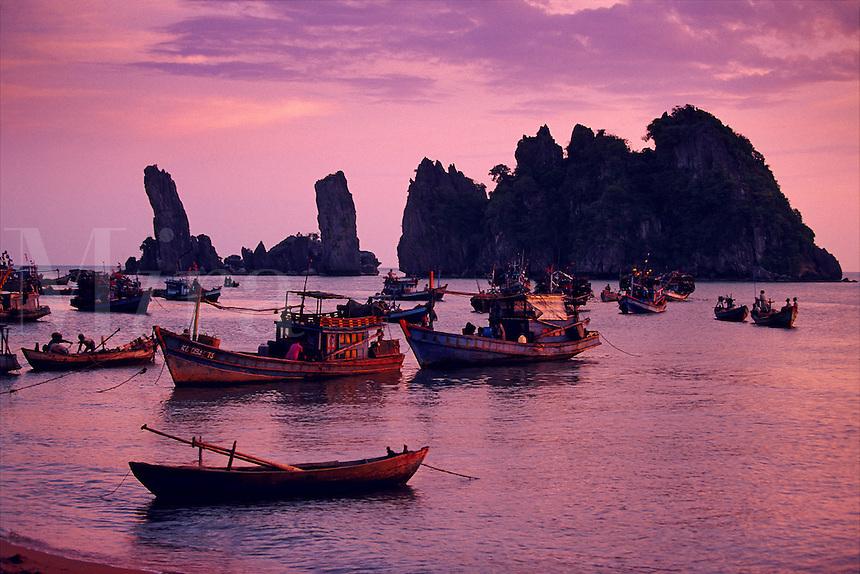Fishing boats at Quong Beach toward Hon Phu Tu rock formations Mekong Delta Vietnam.