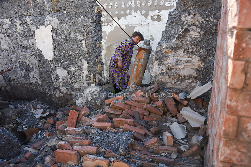 A woman examining  tail of Uragan Rocket in remains of her house, Donetsk, Eastern Ukraine, 16 May, 2015