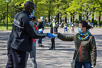 NEW YORK, NY - MAY 10: A police officer wearing a face mask in front of Circle Fence at Flushing Meadow Corona Park on Mother's Day distribute face masks to people on May 10, 2020 in Queens, NY. COVID-19 has spread to most countries in the world, claiming more than 283,000 lives and more than 4.1 million people infected, Queens has been one of the places most affected by the Coronavirus. (Photo by Pablo Monsalve / VIEWpress via Getty Images)