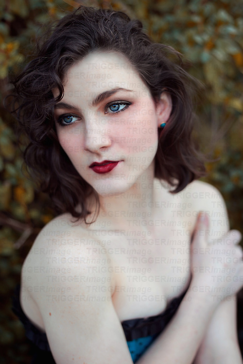 Woman with short curly dark hair staring away from the viewer