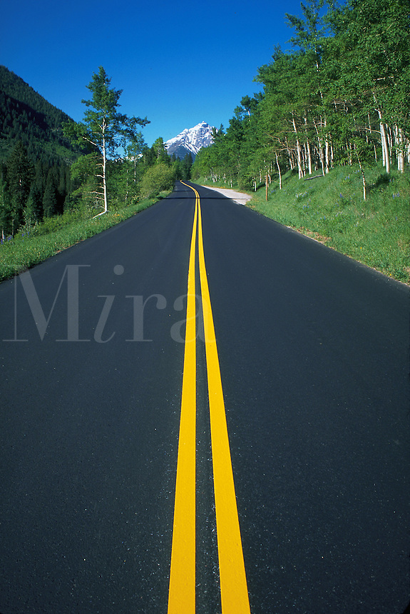 Yellow line in highway with Maroon Bells rock formation in background, Aspen, Colorado