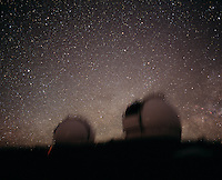 Stars and the Milky Way rising behind the Keck Telescope domes, Mauna Kea, Hawaii.