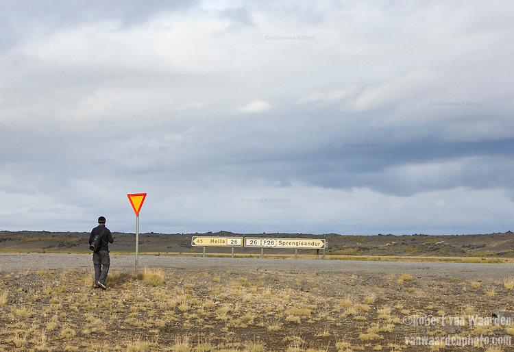 A man stands in front of a yield sign in the Iceland landscape.
