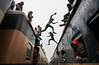 Bangladeshi Muslim boys jump from the top of one overcrowded train to another as thousands of Bangladeshi Muslims try to return home after attending three-day Islamic Congregation on the banks of the River Turag in Tongi, 20 kilometers (13 miles) north of the capital Dhaka, Bangladesh. Hundreds of thousands of Muslims attended the annual three-day event that is one of the world's largest religious gatherings being held since 1960's to revive Islamic tenets. It shuns politics and calls for peace.
