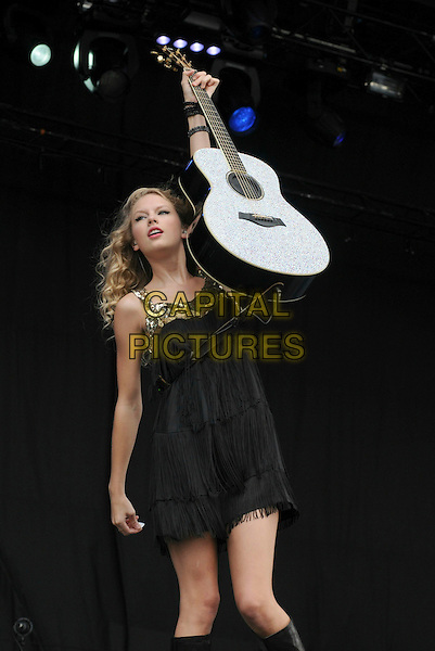 TAYLOR SWIFT.performing live at V Festival 2009 - Day One, Hylands Park, Chelmsford, Essex, .UK, 22nd August 2009..music gig concert on stage half length microphone black dress tassels fringed tassels sequins gold sequined guitar arm in air 3/4 full.CAP/BRC.©Ben Rector/Capital Pictures