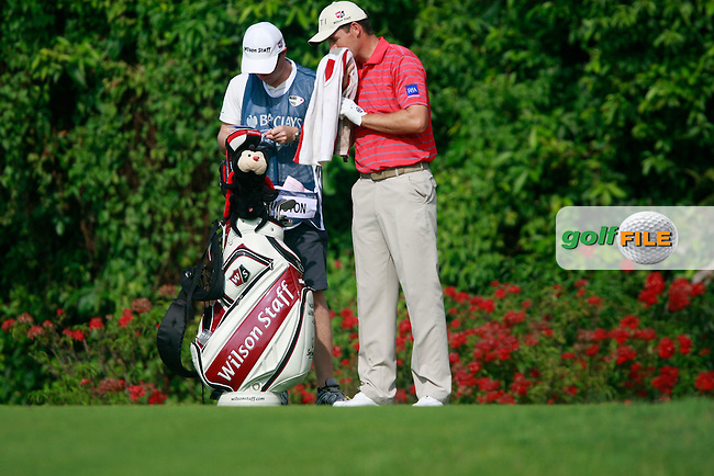Padraig Harrington (IRL) wipes the sweat from his face as caddy Ronan Flood wait on the 1st tee to start their match during Thursday's Round 1 of the 2011 Barclays Singapore Open, Tanjong Course, Sentosa Golf Club, Sentosa Island, Singapore, 10th November 2011 (Photo Eoin Clarke/www.golffile.ie)
