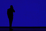 Silhouette of a man talking on cell phone in front of a giant video screen at the North American International Auto Show, 2007