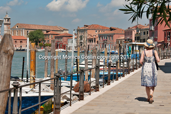 A woman walks along a walkway lined with boats at Murano Island, the glass making island near Venice, Italy