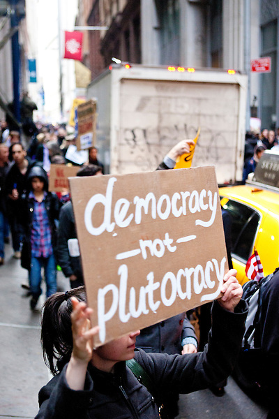 """Hundreds of protesters march early in the morning on November 17, 2011 in New York City with the aim to shut down Wall Street and the Stock Exchange.  The action was the first in a day of protests celebrating the two month anniversary of the """"Occupy Wall Street"""" movement.  While many workers were inconvenienced by the human (and police) barricades, the Stock Exchange opened on schedule."""