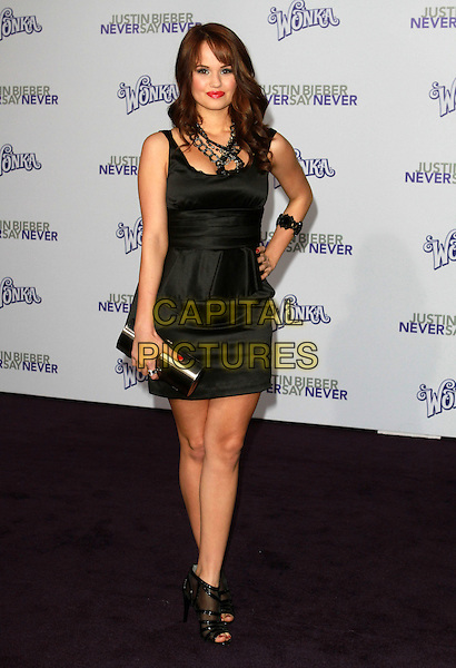 "DEBBY RYAN .Attending ""Justin Bieber: Never Say Never"" Los Angeles Premiere held At Nokia Theatre L.A Live, Los Angeles, California, USA, .8th February 2011..full length black dress peplum hand on hip clutch bag .CAP/ADM/KB.©Kevan Brooks/AdMedia/Capital Pictures."