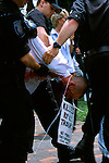 A protester is removed by police during an event in Cambridge, Mass., marking the 230th anniversary of the creation of the Continental Army. The event was held in Cambridge Common, where George Washington first took command of the Continental Army on July 3, 1775.