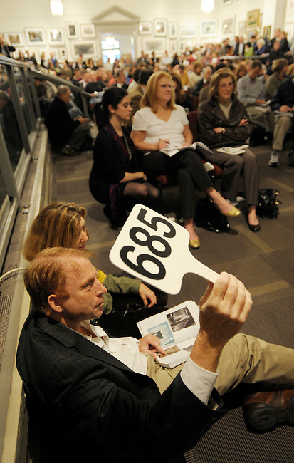 Art buyer Bob Apfell, left and Jai Imbrey, right, makes a bid at  the Freeman's auction house on a peice from the Lehman Brothers Corporate Art Collection November 1, 2009 in Philadelphia. (Bloomberg News/Bradley C Bower)