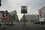 A poster of a Soviet soldiers stares down at passers-by at the site of Checkpoint Charlie. The poster is part of an installation recalling the Soviet and American influence on the formerly-divided city. The Wall was opened 15 years ago on 9th November 1989.