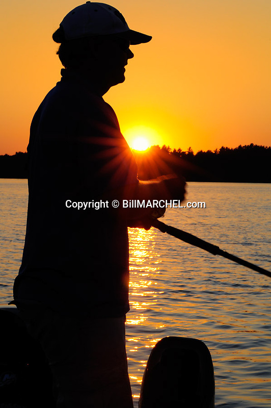 00416-028.19 Fishing:  Angler is silouetted against low sun as he fishes.