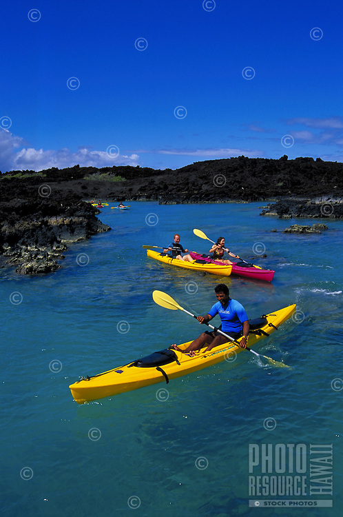Kayaking in La Perouse Bay, the site of the last lava flow on Maui, on Maui's south side, south of Makena and near the Ahihi Marine Preserve. Rough black lava fields dominate this part of the south coastline as is seen behind the kayakers.Kelii's Ka