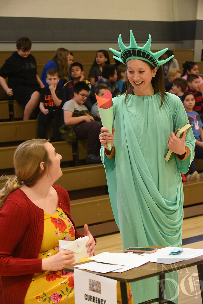 NWA Democrat-Gazette/FLIP PUTTHOFF <br /> ELLIS ISLAND REVISITED<br /> Maggie Peck (left), math facilitator at Frank Tillery Elementary in Rogers, chats Wednesday Feb. 6 2019 with assistant principal Halley Parsons as Parsons plays the Statue of Liberty during a program at the school about Ellis Island and immigration. Third-grade students acted as immigrants in 1910 and visited required stations to enter the United States, said Katelyn Fetner, a teacher at Tillery. Teachers and parents staffed the stations for passport inspection, medical checkups, train tickets and other stops that were at Ellis Island. The island, in Upper New York Bay, was the gateway for over 12 million immigtrants to the United States from 1892 to 1954.