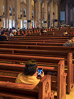 A girl playing with her cell phone Inside the Baclaran Church in Manila, Philippines