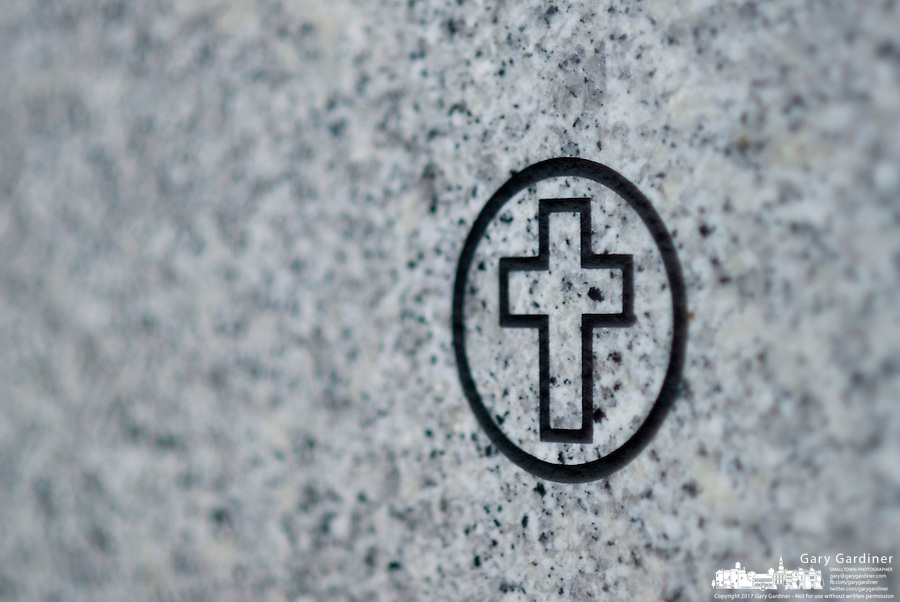 A cross adorns the marble covering on a mausoleum cover.<br />