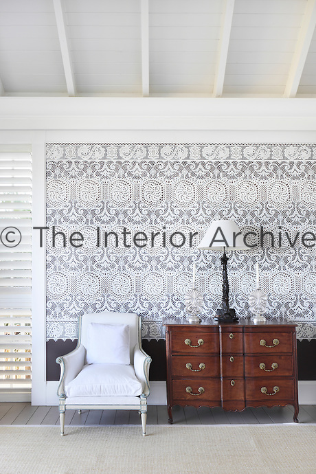 Detail of an antique chest of drawers and a chair in one of the spacious, light bedrooms decorated with a lacework patterned wallpaper