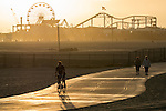 A man rides a bicycle on the bike path near the Santa Monica Pier. The Santa Monica Pier is a prominent 100-year-old landmark and tourist destination that includes the roller coaster and ferris wheel at the Pacific Park amusement park on the pier.