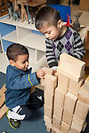 Education preschool 3-4 year olds two boys building block construction together