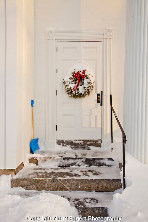 A shovel leans against the church after being used to clear a path through the snow.