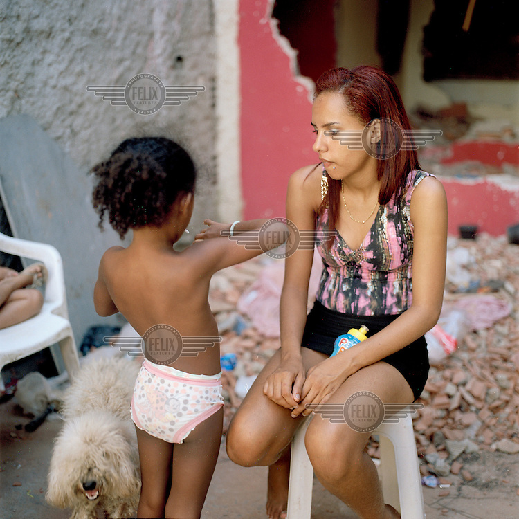 A woman and a child sit among the rubble in the Largo do Tanque favela. Residents of Largo do Tanque have undergone forced evictions and the demolition of their homes in to make room for the Transcarioca Highway, that will eventually be built to accommodate the 2016 Olympics. In less than two weeks, 54 houses were demolished with sledgehammers and bulldozers. The city assessor sent to handle negotiations told residents not to speak with one another or seek legal advice otherwise he would reduce settlement offers. Many residents agreed to compensations of around BRL 7000 (USD 3500).
