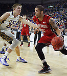SIOUX FALLS, SD - MARCH 9: Tyler Larson #55 of USD drives against defender Reed Tellinghuisen #23 of SDSU in the first half of their semi-final round Summit League Championship Tournament game Monday evening at the Denny Sanford Premier Center in Sioux Falls, SD. (Photo by Dick Carlson/Inertia)