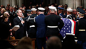 Former President George W. Bush places his hand over his heart  as the flag-draped casket of former President George H.W. Bush is carried by a joint services military honor guard after the State Funeral at the National Cathedral, Wednesday, Dec. 5, 2018, in Washington. At left is Laura Bush. <br /> Credit: Alex Brandon / Pool via CNP