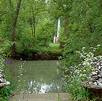 A glimpse of an obelisk across the water through a gap in the trees in the garden