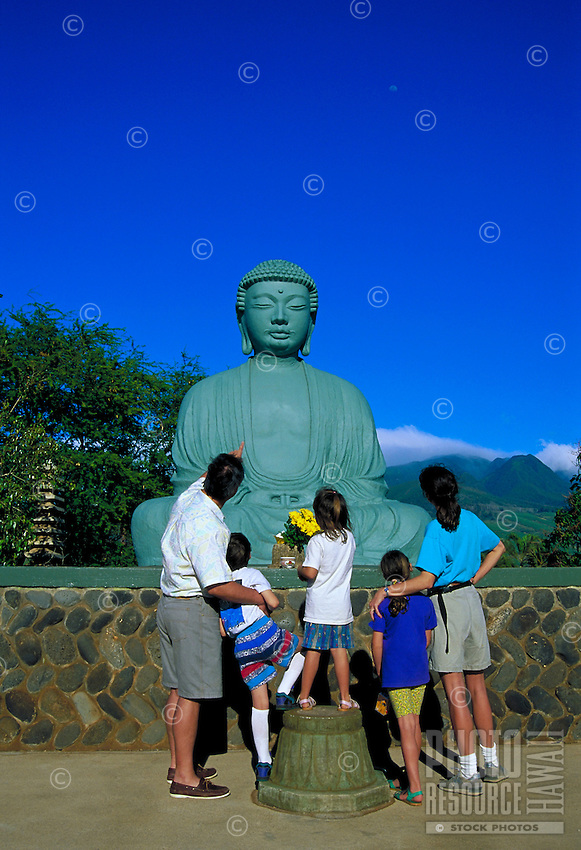 A family converses about the bronze Buddha statue at the Jodo Mission in Lahaina, Maui.