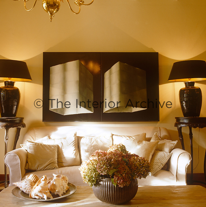 A pair of black lamps on pedestal tables frame an oil painting by Paul de Vilder hanging on the wall in the living room