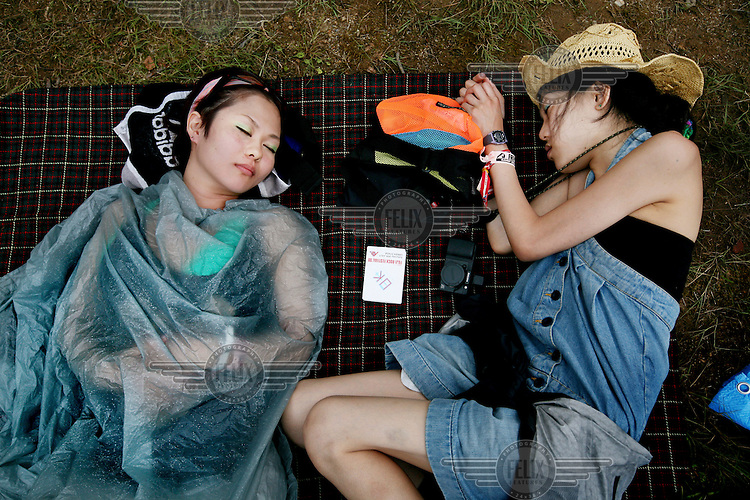 Two festival goers at the Fuji Rocks music festival sleep on a blanket.