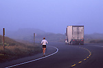 Runner on highway in fog with truck on road, near Manila, Samoa Peninsula, Humboldt County, CALIFORNIA