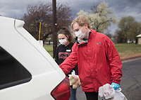 """Serena Doles, 16, of Bentonville (from left) and Josiah Doles, 19, distribute food, Thursday, March 19, 2020 at the Samaritan Community Center in Rogers. Check out nwaonline.com/200320Daily/ for today's photo gallery.<br /> (NWA Democrat-Gazette/Charlie Kaijo)<br /> <br /> In response to the covid-19 crisis, Samaritan decided to convert all of their feeding operations to drive through operations. They started on Monday in Springdale and expanded to Rogers on Tuesday. They are running their Cafe by providing hot meals, running their market by providing groceries and running their snack pack program by providing snack packs along with the groceries people pick up. Compared to a normal week, they've doubled their numbers in Rogers and tripled their numbers in Springdale. Running Monday through Thursday. """"We're trying to do the same thing we always do. We're just serving more people,"""" said Debbie Rambo, executive director. Since revenue is down from their thrift stores, their main funding sources, they are asking people to donate by visiting samcc.org. People can also donate over the phone or they can mail a check to P.O. Box 939 in Rogers, 72757"""