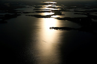 Sparkling afternoon light reflects on waves as a single boat crosses the composition. Aerial of Lake Minnetonka in Minnesota, USA.