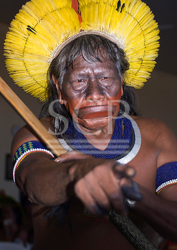 Colider, Mato Grosso State, Brazil. Cacique Raoni Txucarrhamae with yellow feather cocaa, botoque lip plate and borduna at a meeting with government officials from Brasilia.