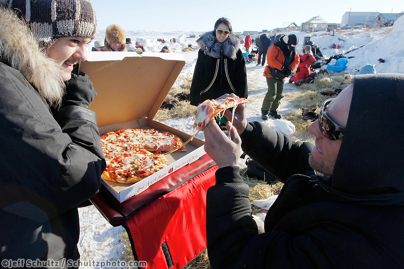 Sven Haltman is greeting at the Unalakleet checkpoint with a hot pizza on Sunday during Iditarod 2011.