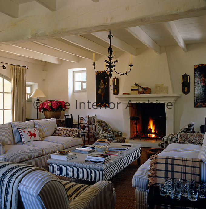 The whitewashed rustic sitting room is furnished with comfortable sofas and chairs upholstered in a striped fabric