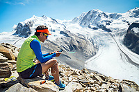 Sitting at the Gornergrat with views of the Monte Rosa, a man uses a battery to charge his phone for use. Switzerland.