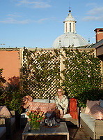 A portrait on Alessandra Branca on the roof terrace. The 1614 Chiesa della Santissima Trinità dei Pellegrini is just behind a jasmine-covered trellis on the terrace; the sofas and cushions are by Manutti.