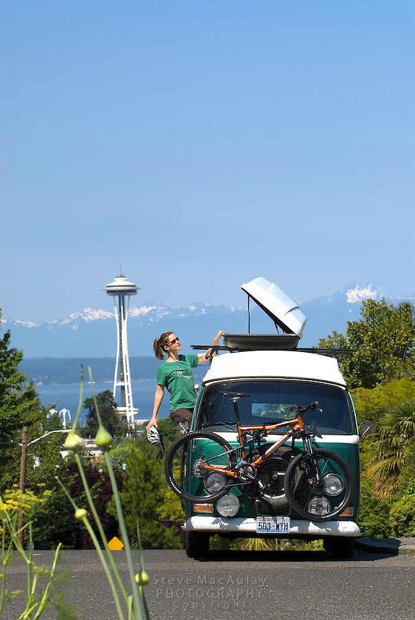 Young woman unloading mountain bike gear from roof box on old V.W. bus with the Space Needle and Olympic Mountains visible behind.  Seattle, WA.